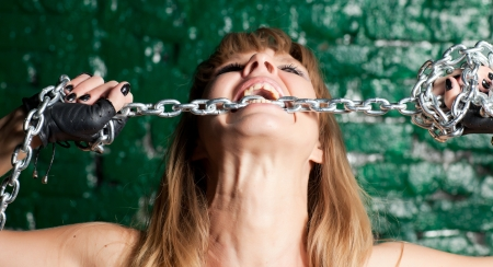 beautiful woman with a steel chain in his mouth against the wall Stock Photo - 21305116