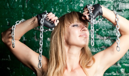 beautiful woman with an steel chain on the background wall Stock Photo - 21305117