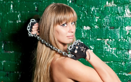 beautiful woman with an steel chain on the background wall Stock Photo - 21305126