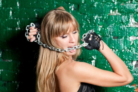 beautiful woman with an steel chain on the background wall Stock Photo - 21305127