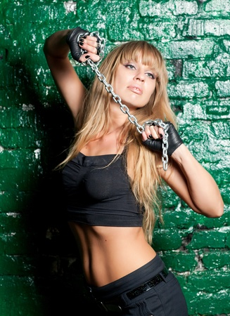 beautiful woman with an steel chain on the background wall photo