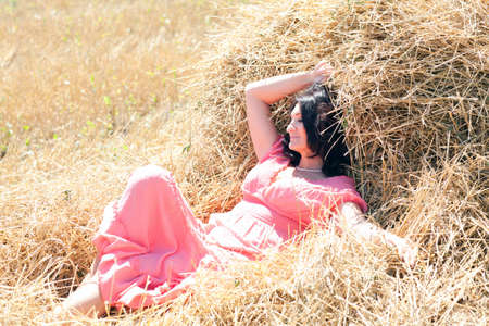 aciculum: beautiful adult woman in pink sundress is resting in the hay Stock Photo