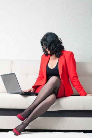 suit skirt: adult beautiful business woman in a red suit sitting on the couch with laptop. business woman in a strict jacket and skirt