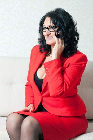 beautiful business woman in a red suit talking on a cell phone photo
