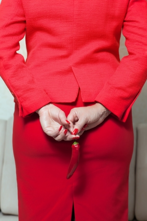 woman in a red suit stands back and keeps the red pepper