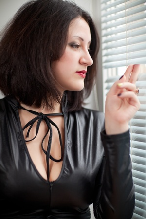 girl in a black dress at a window looking through the blinds photo