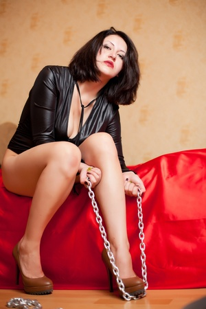 beautiful young woman sitting on a couch and holding a chain Stock Photo - 22106553