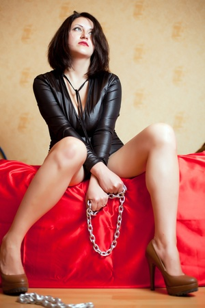 beautiful young woman sitting on a couch and holding a chain Stock Photo - 22106554