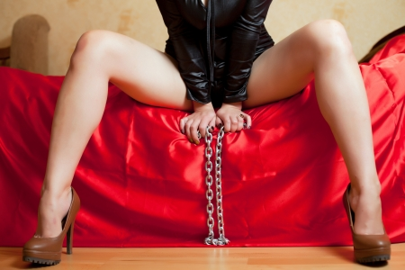 domination: beautiful young woman sitting on a couch and holding a chain