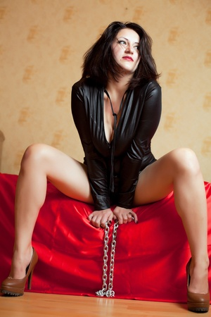 beautiful young woman sitting on a couch and holding a chain photo