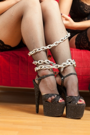 young woman sitting on the couch with a chain on his feet photo