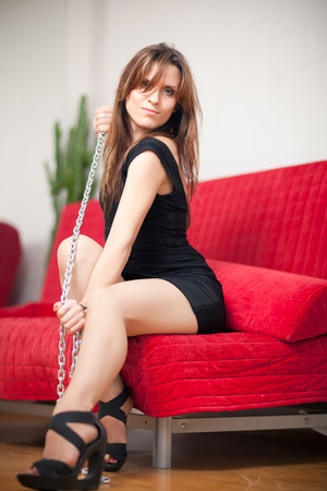 young beautiful woman sitting on a red couch and holding a steel chain Stock Photo - 22549892