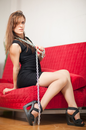 young beautiful woman sitting on a red couch and holding a steel chain Stock Photo - 22549895