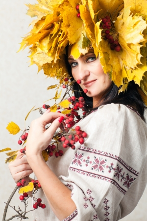 beautiful adult woman with a wreath of autumn leaves photo