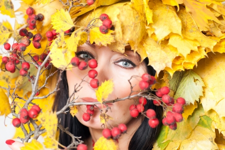 face of a beautiful woman in yellow autumn leaves and red berries photo