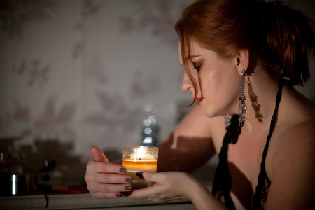 young beautiful woman holding a candle in her hands Stock Photo