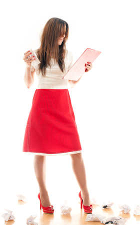 transcribe: Attractive business woman pulling out sheets of notebook while standing on a white background