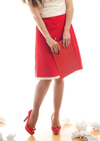 screenwriter: business woman pulling out sheets of notebook while standing on a white background