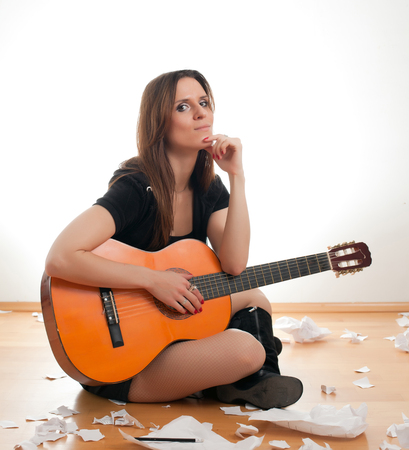 young woman with guitar sitting on floor and writes. woman writes a song photo