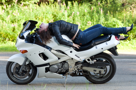 young beautiful woman lying on a sports biker white motorcycle next to the road
