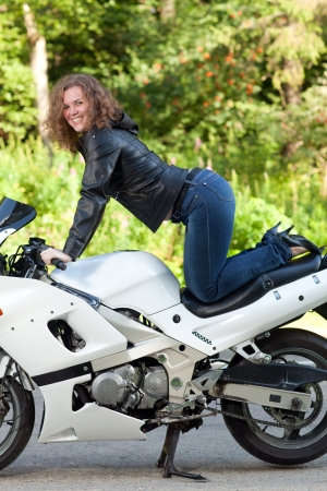 beautiful young female biker sitting on a sports motorcycle
