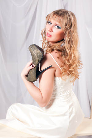 beautiful woman in a white dress cuddle high-heeled shoes photo