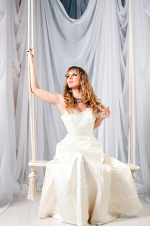 beautiful woman in white dress sitting on a swing in the studio photo