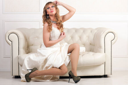 beautiful woman in a long white dress sitting on a sofa photo