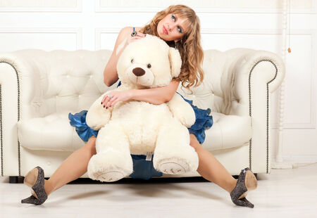 woman sitting on a couch and holding a teddy bear photo