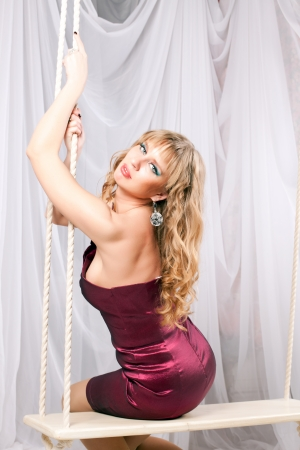woman in a short dress sitting on a swing in the studio photo