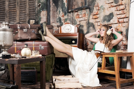 beautiful woman in a white dress sitting in a chair and listening to music with headphones in the old room