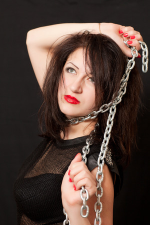 beautiful young woman with a chain around his neck on a black background