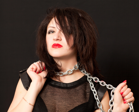 beautiful young woman with a chain around his neck on a black background photo