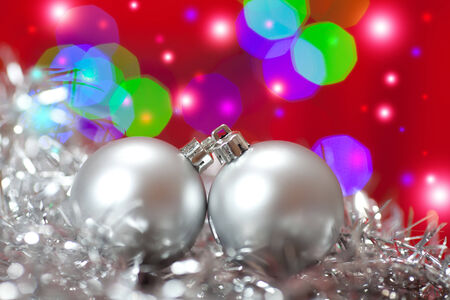 Close up of a silver Christmas ornament in shiny Christmas tinsel, with lights.  photo
