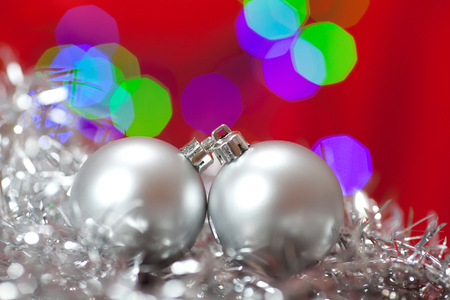 Close up of a silver Christmas ornament in shiny Christmas tinsel, with lights in the background.  photo
