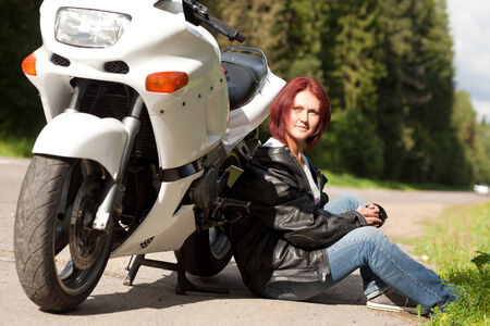 young attractive woman sits near a sports bike near road photo