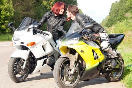 young man and woman kissing while sitting on motorcycles. young couple traveling on motorcycles photo