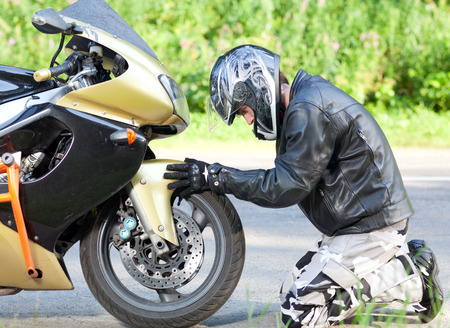 man on his knees near a sports bike on the road Stock Photo