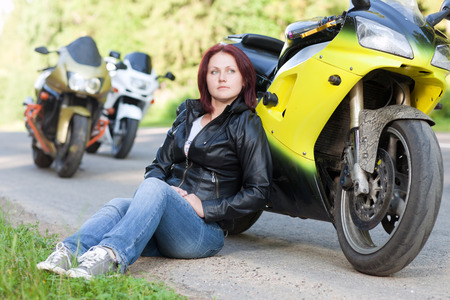 beautiful young woman sitting at the roadside near the sports motorcycle