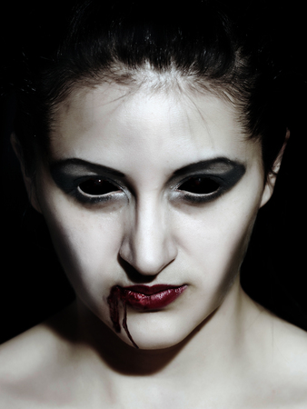 Portrait of a female vampire. Halloween theme. Demon woman, closeup face photo