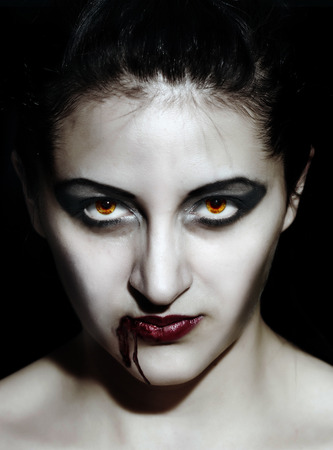 Portrait of a female vampire. Halloween theme. Demon woman, closeup face