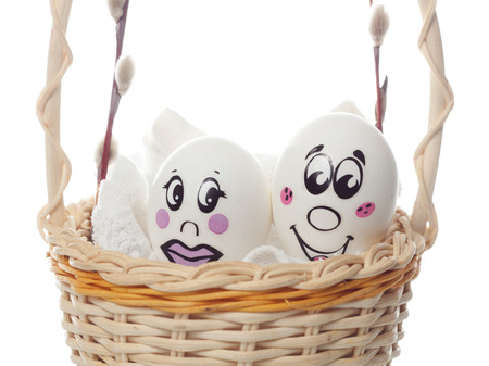 Easter eggs with painted faces and emotions in a basket on a white