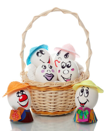 breakfast smiley face: Easter eggs with painted faces and emotions in a basket on a white