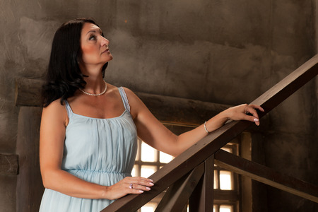 leans: beautiful adult woman in dress leans on the railing  Stock Photo