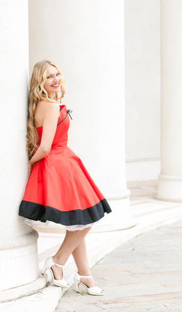 leans on hand: beautiful young woman in a red dress leans on a white column Stock Photo
