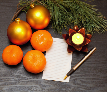 List on a wooden table candle and Christmas decorations photo