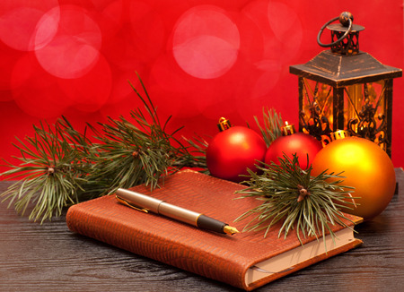 Fountain pen on a notebook on a wooden table and Christmas decorations 版權商用圖片 - 34606168