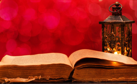Opened old book and candle lantern on a red background with bokeh photo