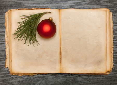 open old book and christmas ball on a wooden table photo