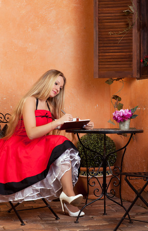 beautiful young woman with a notebook sitting at a table photo